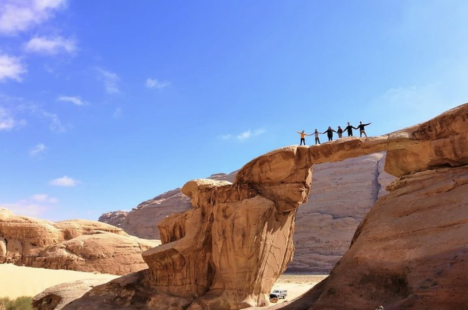 Wadi Rum from Petra - People Standing on a Rock Arch in Wadi Rum