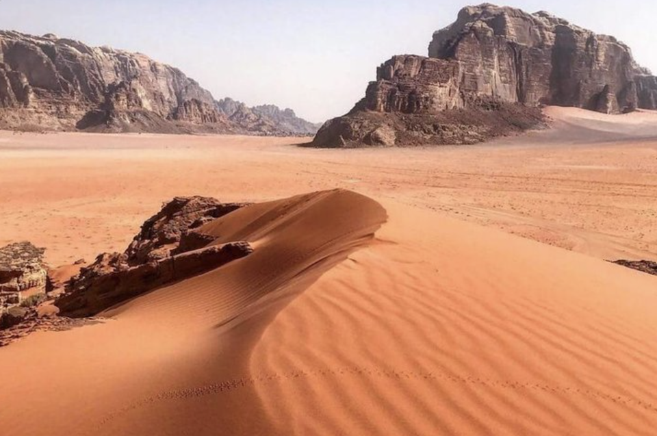 Wadi Rum from Petra - A Sand Dune and Towering Rock Formations Beyond
